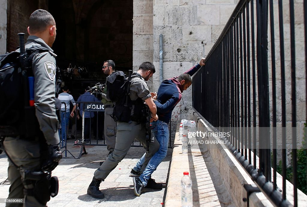 A Palestinian man is frisked by Israeli border police at Damascus Gate at the entrance of the Muslim quarter of Jerusalem's Old City on May 6, 2016. / AFP / AHMAD