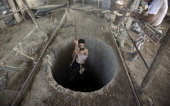 A Palestinian man is lowered into a smuggling tunnel beneath the GazaEgypt border in the southern Gaza Strip on September 11 2013 Egyptian security...
