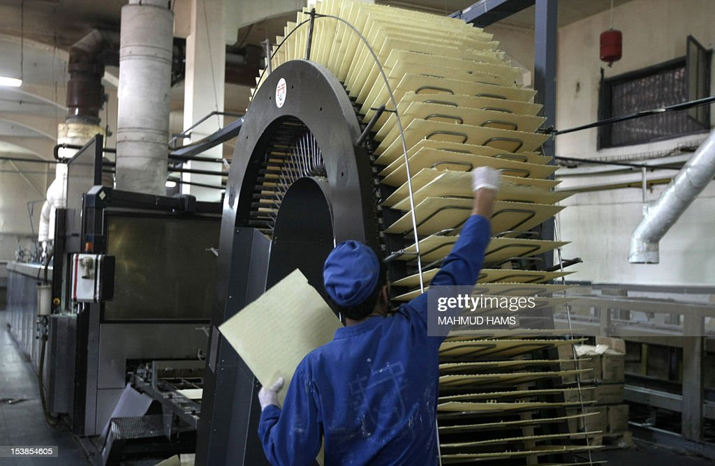 A Palestinian man is seen working at the al-Awda Biscuit factory in Deir al-Balah, in the central Gaza strip, on October 10, 2012. The World Food Program (WFP) will export the biscuits to United Nation run schools in the Israeli occupied Palestinian West Bank, the first time since 2006 when the Gaza Strip was put under an Israeli blockade. AFP PHOTO / MAHMUD HAMS