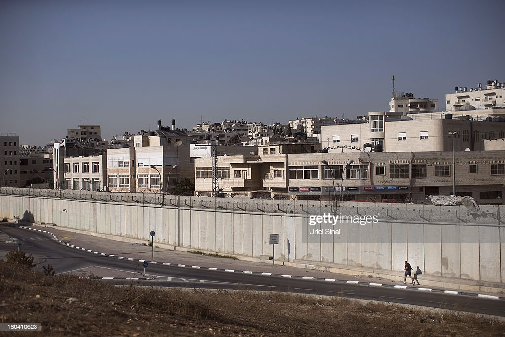 A Palestinian man jogs along the Israeli West Bank barrier on the outskirts of Jerusalem on September 12, 2013 in Aram, West Bank. The twenty-year anniversary of the Oslo Accord, which was to set up a framework for peace between Israel and Palestine, will be marked on September 13.