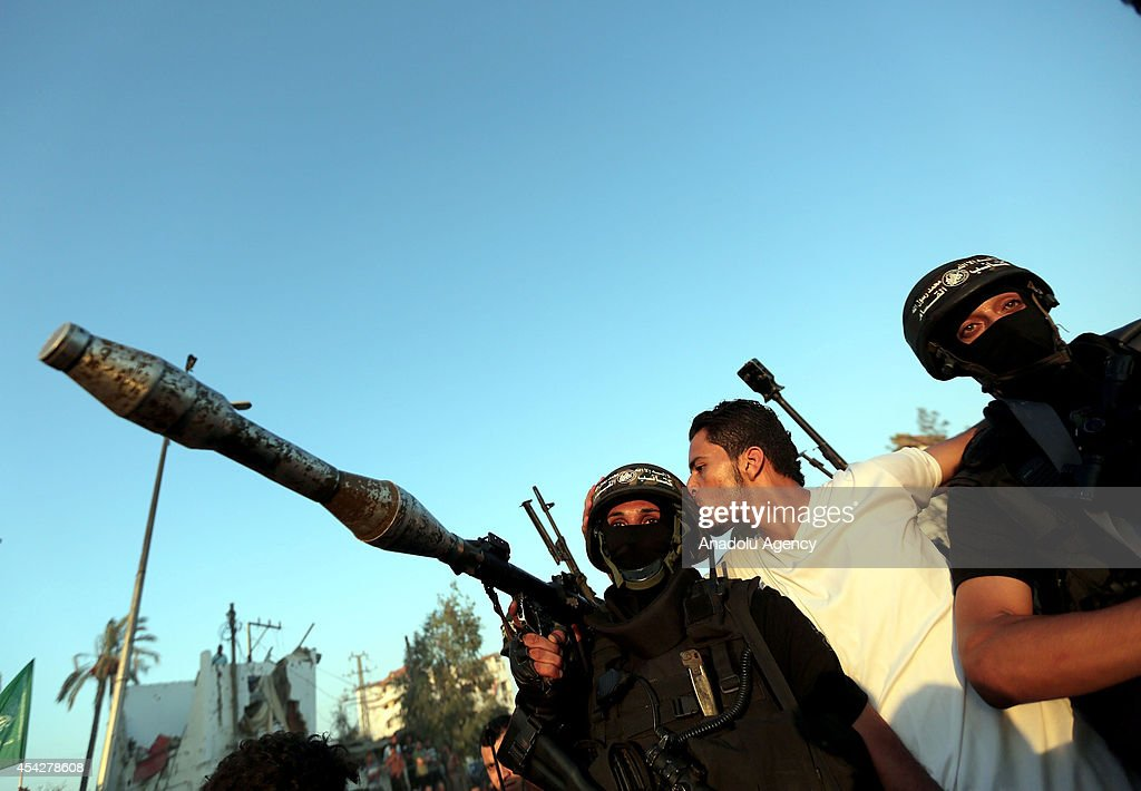 Palestinian man kisses a member of the Ezzeddin al-Qassam Brigades, the armed wing of Palestinian resistance faction Hamas, during their press statement in the Shujaya neighborhood in eastern Gaza City on August 27, 2014.