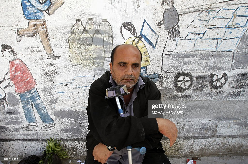 A Palestinian man leans on his crutch as he waits for aid at a UN supplies center after it was damaged in an Israeli airstrike directed at the nearby Hamas police headquarters at the Jabalya refugee camp, in the northern Gaza Strip on November 20, 2012. Israel halted a threatened Gaza ground offensive to give Egyptian-led truce talks a chance as top diplomats flew in to boost efforts to end nearly a week of cross-border violence. AFP PHOTO/MOHAMMED ABED