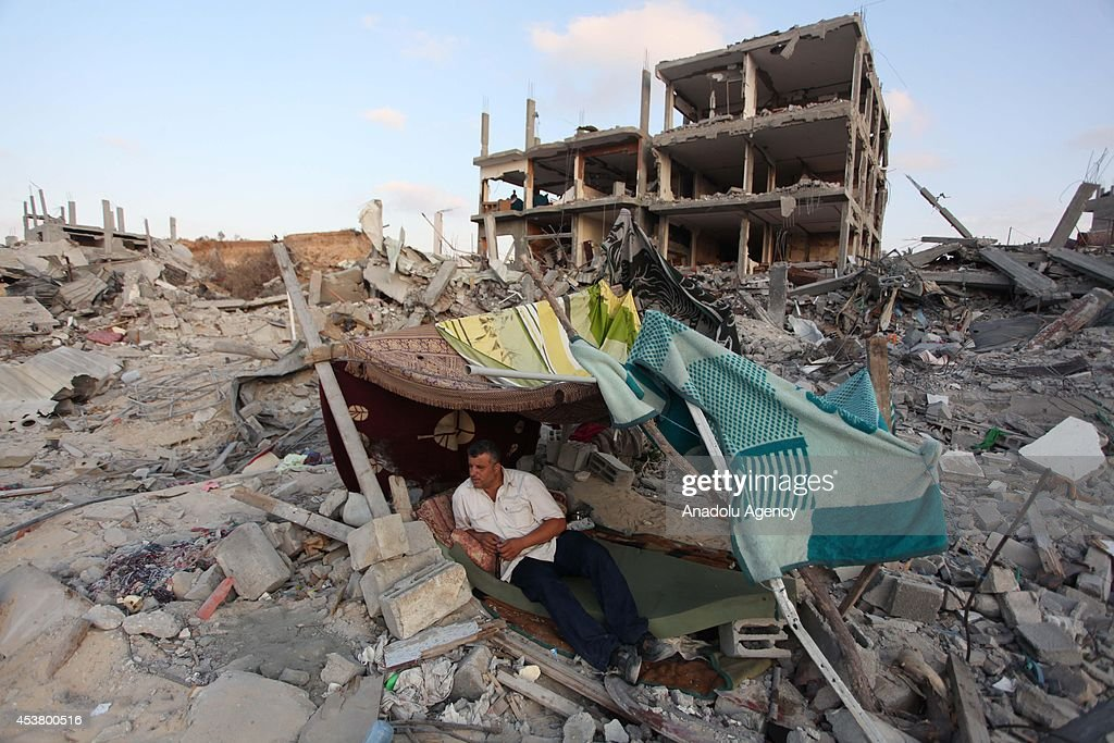A Palestinian man lies in a tent among the heavy destruction and the debris of buildings destroyed in Israeli shelling in Al Shaaf neighborhood of Gaza City, Gaza on August 18, 2014.