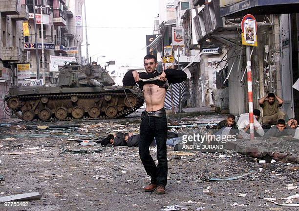 A Palestinian man lifts up his shirt in front of Israeli troops 30 March 2002 in the West Bank city of Ramallah following an allnight street battle...