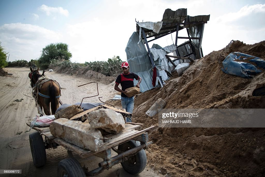 A Palestinian man loads stones on a cart next to a crater on August 22 2016 in Beit Lahia in the northern Gaza Strip following an Israeli airstrike...