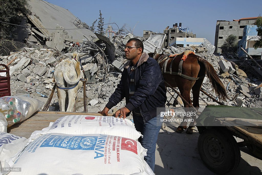 A Palestinian man loads up his horse drawn cart with aid from a UN supplies center, after it was damaged in an Israeli airstrike directed at the nearby Hamas police headquarters at the Jabalya refugee camp, in the northern Gaza Strip on November 20, 2012. Israel halted a threatened Gaza ground offensive to give Egyptian-led truce talks a chance as top diplomats flew in to boost efforts to end nearly a week of cross-border violence.