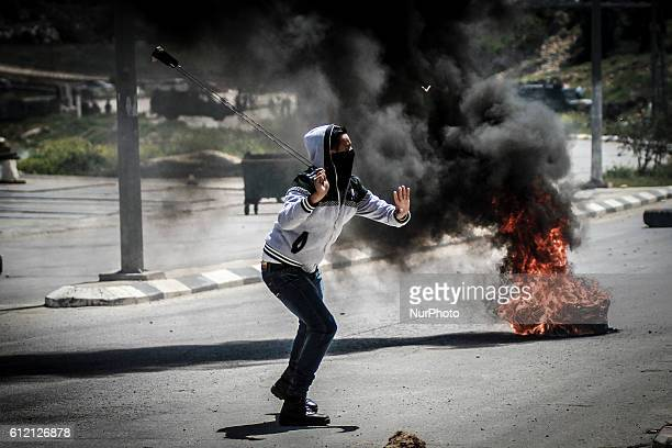 Palestinian man lobs a stone against Israeli soldiers during clashes close to the Israeli military prison of Ofer near the village of Betunia in the...