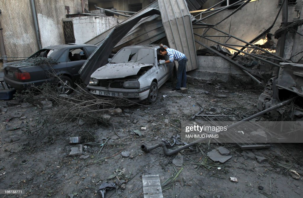 A Palestinian man looks at a damaged vehicle parked outside a destroyed branch of the Islamic National Bank following an Israeli air strike in Gaza City, on November 20, 2012. Seven Palestinians were wounded in strikes on Gaza overnight, but no one was killed in the first night without fatalities since the Israeli air campaign began nearly a week ago.