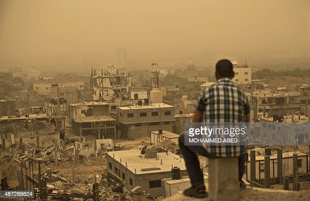 A Palestinian man looks at the rubble of buildings which were destroyed during the 50day war between Israel and Hamas militants in the summer of 2014...