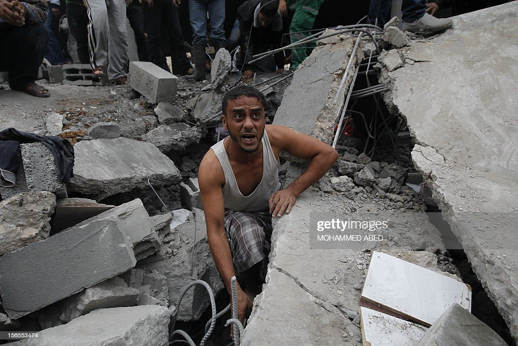 A Palestinian man looks for injured people in the rubble following an Israeli air raid on a house in Beit Lahia, the northern Gaza Strip on November 17, 2012. Israeli air strikes hit the cabinet headquarters of Gaza's Hamas government, the group said early on November 17, with eyewitnesses reporting extensive damage to the building. AFP PHOTO / MOHAMMED ABED