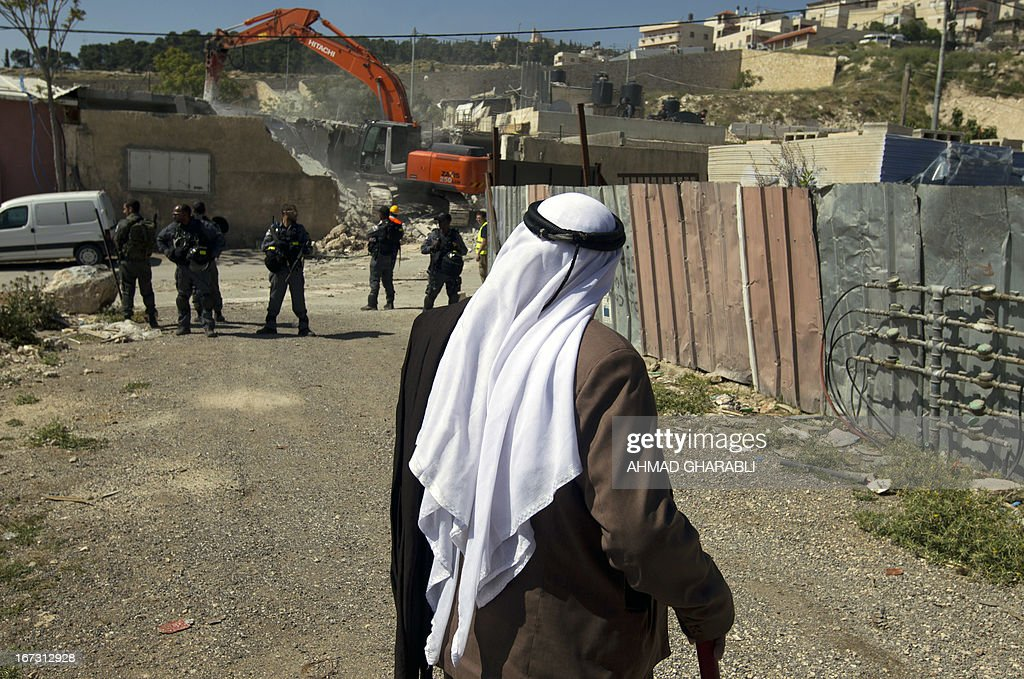 A Palestinian man looks on as his house is demolished by a bulldozer hired by the Jerusalem municipality in the Israeli annexed East Jerusalem neighbourhood of al-Tur on April 24, 2013. Palestinian homes built without a construction permit are often demolished by order of the Jerusalem municipality.