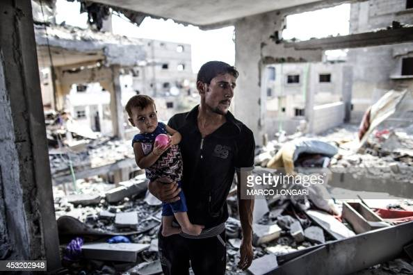 A Palestinian man looks on while standing in what remains of his house in part of the northern Beit Hanun district of the Gaza Strip after a 72hour...