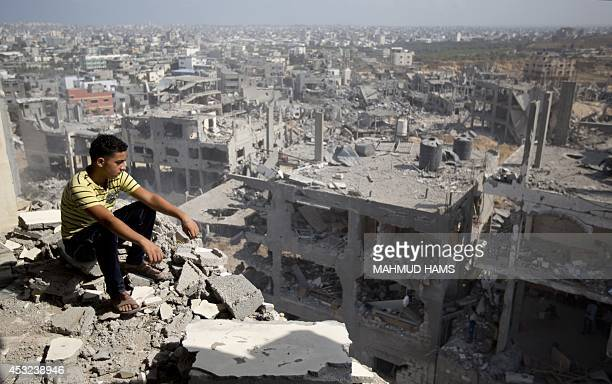 A Palestinian man looks out over destruction in part of Gaza City's alTufah neighbourhood as the fragile ceasefire in the Gaza Strip entered a second...