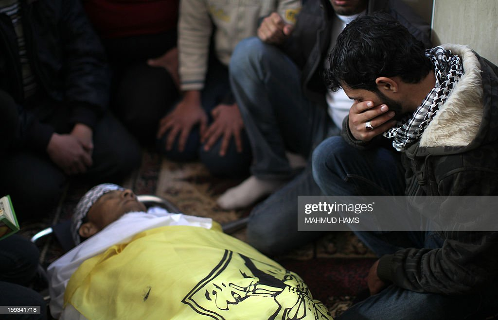 A Palestinian man mourns over the body of Anwar Mohammed al-Mamluk during his funeral in Gaza City on January 12, 2013. Israeli soldiers shot dead Mamluk and wounded another in the northern Gaza Strip, a spokesman for the territory's emergency services said.