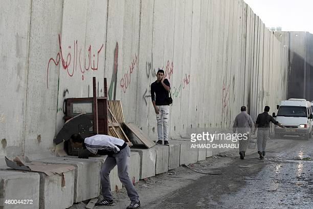 A Palestinian man peeks through a hole of a new section of Israel's controversial separation barrier in the Shuafat refugee camp in east Jerusalem on...