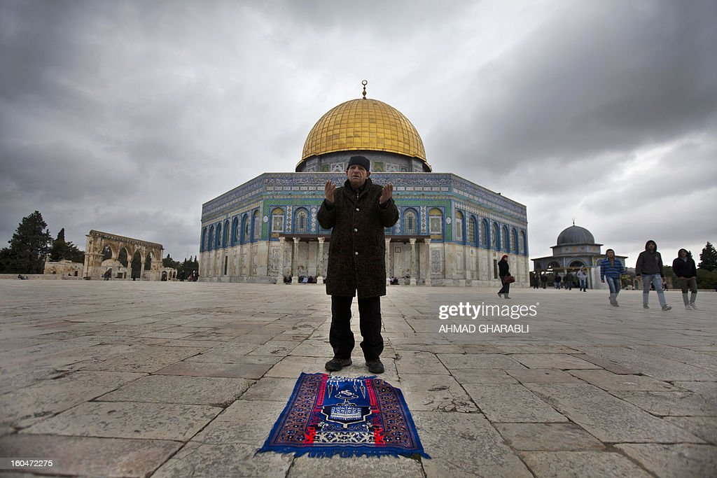 A Palestinian man performs the weekly Muslim Friday prayers outside the Dome of the Rock at the Al-Aqsa mosque compound in Jerusalem on February 1, 2013. AFP PHOTO/AHMAD GHARABLI