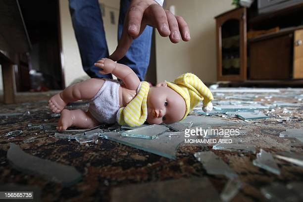 A Palestinian man picks up a doll lying on shattered glass in a damaged house following an Israeli air raid in Gaza City on November 17 2012 Israeli...