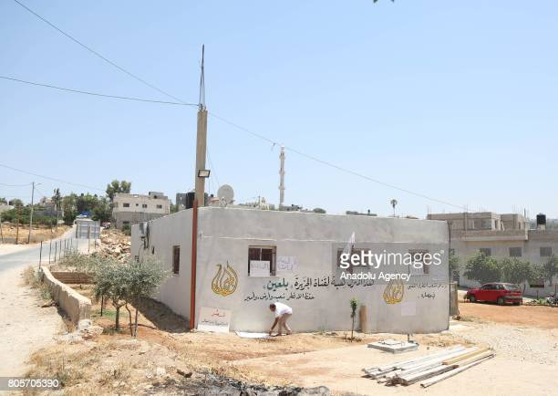 Palestinian man places placards to the wall of a house after Palestinian farmer Ayid Burnat donates his house to Dohabased Al Jazeera Television to...