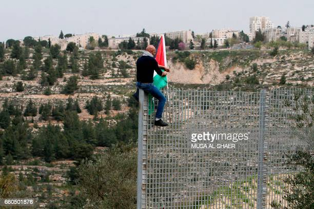 Palestinian man plants his national flag atop an iron fence setup by Israeli security forces between the Palestinian village of Beit Jala and the...