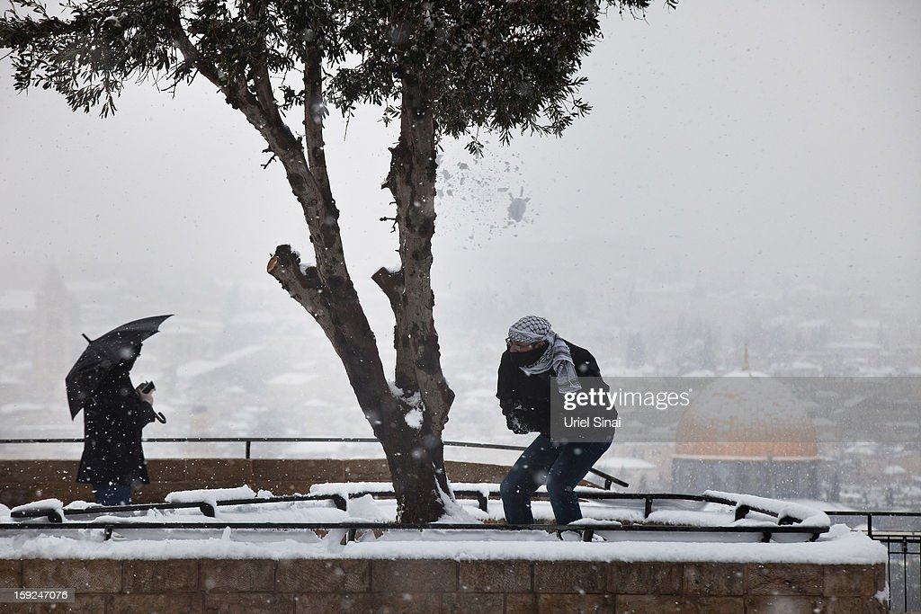 A Palestinian man plays in the snow as it covers the Dome of the Rock at the Al-Aqsa mosque compound behind him on January 10, 2013 in the old city in east Jerusalem, Israel.