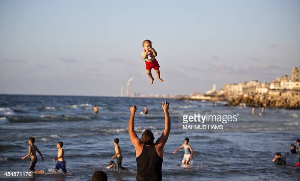 A Palestinian man plays with his baby on a beach on September 7 2014 in Gaza city AFP PHOTO/MAHMUD HAMS