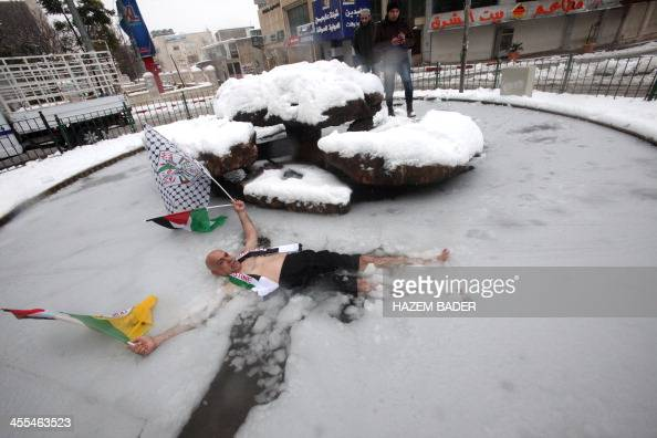 A Palestinian man poses for pictures with his national and the Fatah party flags as he lies in a halffrozen fountain in the West Bank town of Hebron...