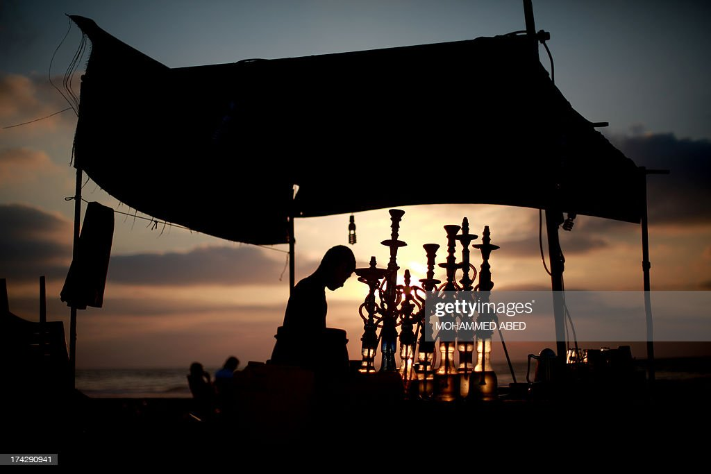A Palestinian man prepares water pipes as the sun sets over the Gaza Strip on July 23, 2013, ending a day of fasting during the holy Muslim month of Ramadan. Following the Iftar diner which breaks the day long fast, people will come to the sea front to relax, eat ice cream and smoke water pipes. Throughout the month, devout Muslims must abstain from food and drink from dawn until sunset when they break the fast with the Iftar meal. AFP PHOTO/MOHAMMED ABED