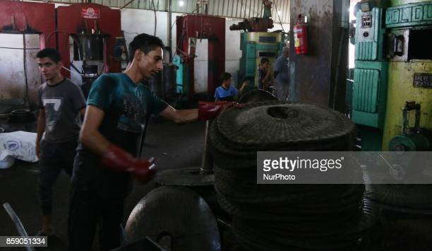 A Palestinian man presses olives by a machine to be made into oil at an olive press in Gaza City on October 8 2017 Farmers harvest their olives this...