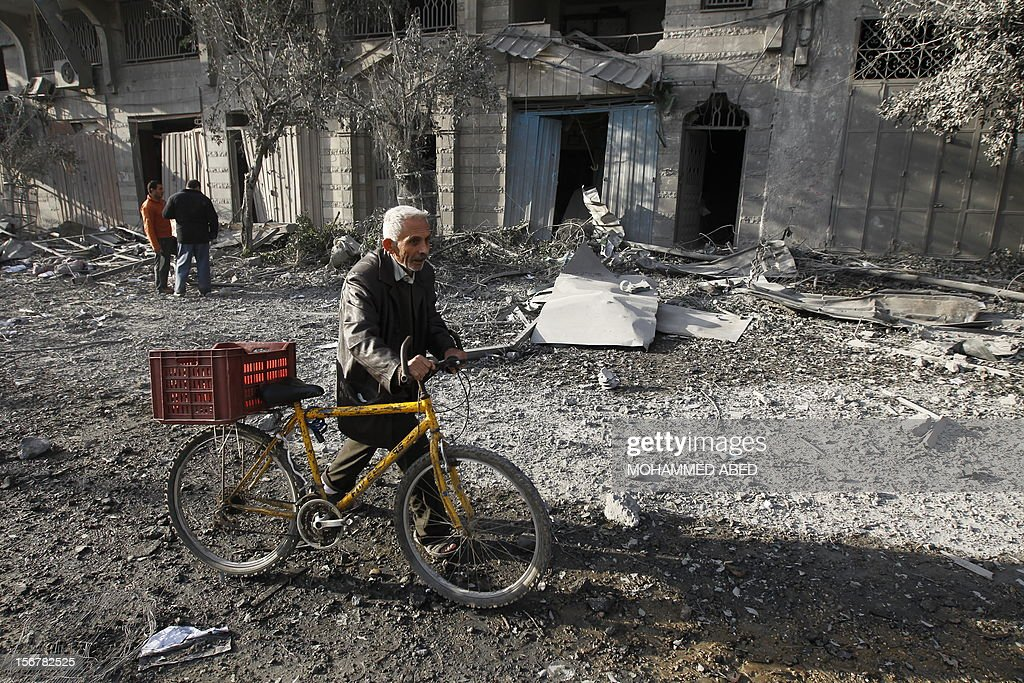 A Palestinian man pushes his bicycle amidst debris near the destroyed compound of the internal security ministry in Gaza City after it was targeted by an Israeli air strike overnight on November 21, 2012. Fighting raged on both sides of Gaza's borders Wednesday despite intensified efforts across the region to thrash out a truce to end a week of violence that has cost 136 Palestinian and five Israeli lives.
