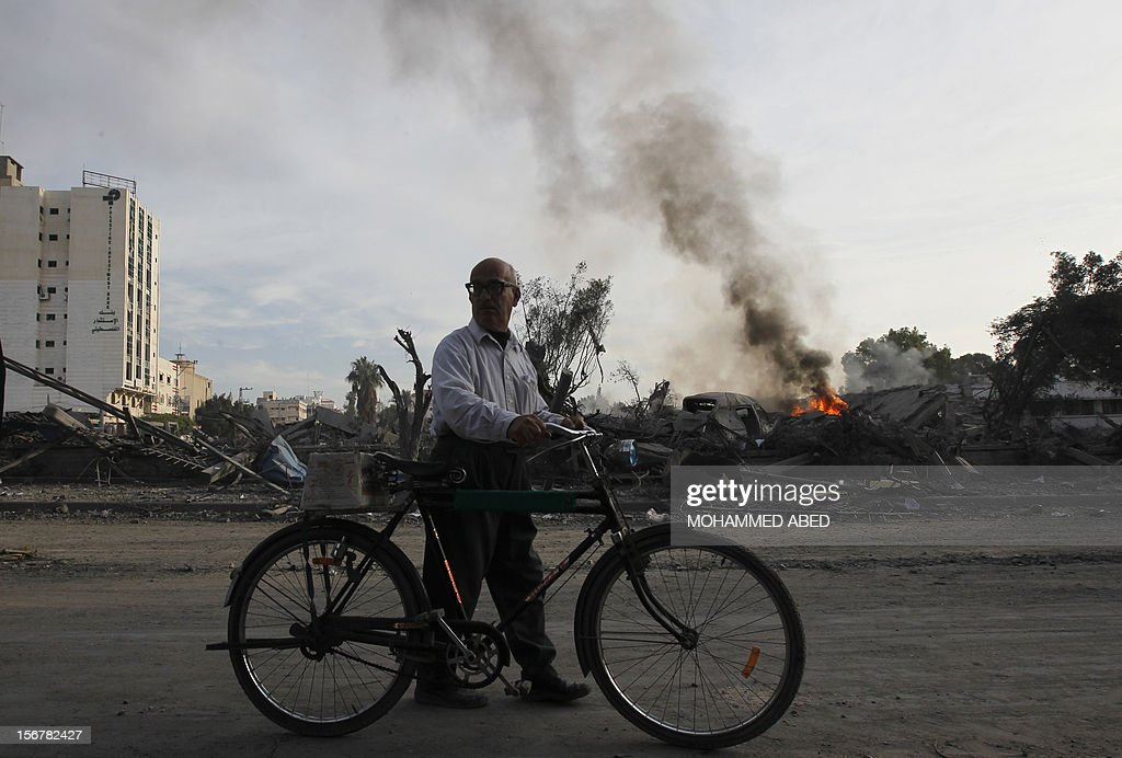 A Palestinian man pushes his bicycle past burning debris at the destroyed compound of the internal security ministry in Gaza City after it was targeted by an Israeli air strike overnight on November 21, 2012. Fighting raged on both sides of Gaza's borders Wednesday despite intensified efforts across the region to thrash out a truce to end a week of violence that has cost 136 Palestinian and five Israeli lives.
