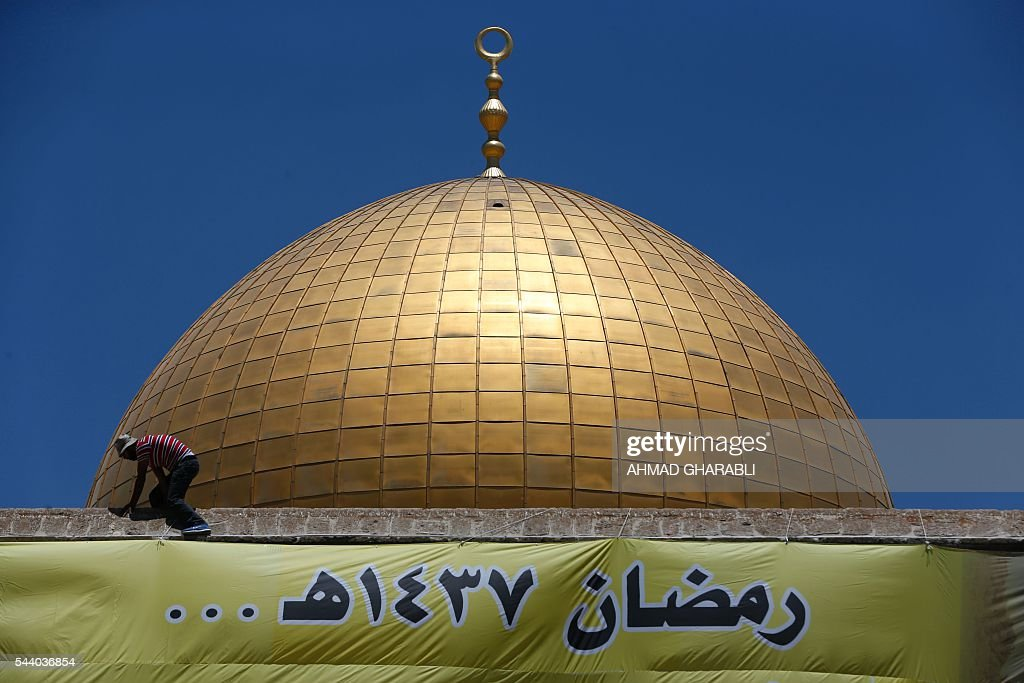 A Palestinian man puts up a banner on the front side of the Dome of the Rock in Jerusalem's Al-Aqsa mosque compound during the last Friday prayers of the holy Muslim fasting month of Ramadan, on July 1, 2016. The writing in Arabic reads: 'Ramadan 1437 A.H... and still the Al-Aqsa waits for someone to liberate it'. / AFP / AHMAD