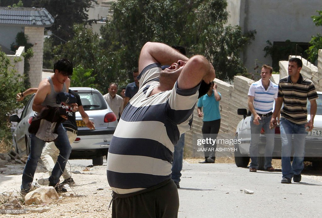 A Palestinian man reacts after his son was injured by tear gas during clashes following a protest against the expropriation of Palestinian land by Israel on May 31, 2013 in the village of Kfar Qaddum, near the occupied West Bank city of Nablus.