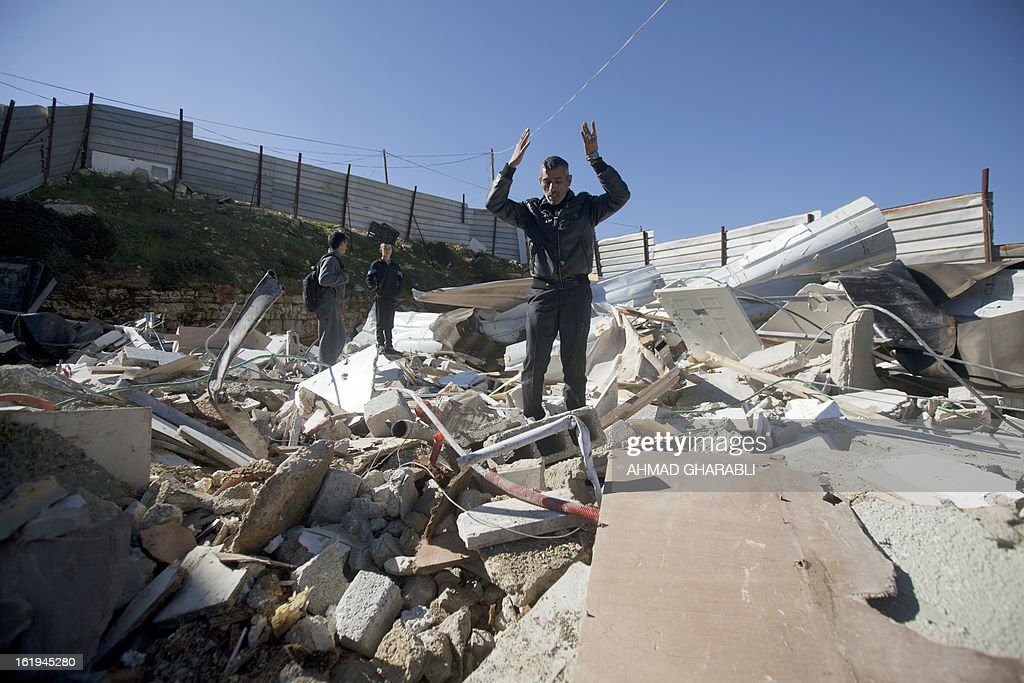 A Palestinian man reacts as he walks on the debris of his home after Israeli bulldozers demolished the house in the Arab East Jerusalem neighborhood of Beit Hanina on February 18, 2013. Palestinian homes built without a construction permit are often demolished by order of the Jerusalem municipality. AFP PHOTO/AHMAD GHARABLI