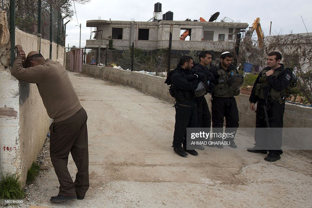 A Palestinian man reacts near Israeli security forces after Israeli bulldozers demolished his family house in the Arab east Jerusalem neighborhood of Beit Hanina on February 5, 2013. Palestinian homes built without a construction permit are often demolished by order of the Jerusalem municipality.