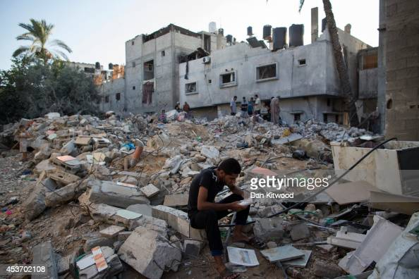 Palestinian man reads items found in the rubble of a destroyed area of housing on August 16 2014 in Gaza City Gaza A fiveday ceasefire between...
