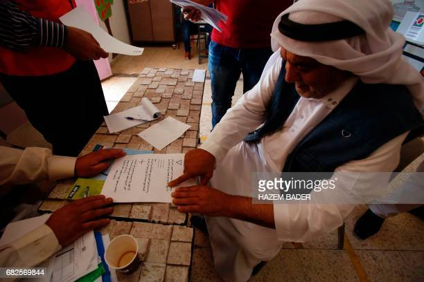 A Palestinian man reads the Braille translation of the voting procedure at a polling station during the municipal elections in the village of Yatta...