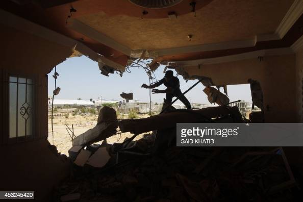 A Palestinian man removes by hand rubble from a destroyed home following an earlier Israeli air strike in Rafah in the southern Gaza Strip on August...