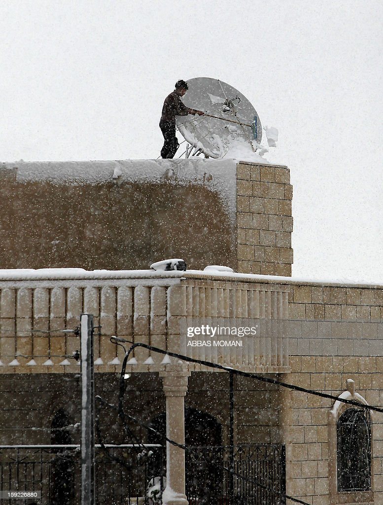 A Palestinian man removes snow covering a satellite dish on the rooftop of a building in the West Bank city of Ramallah on January 10, 2013. Abnormal storms which have blasted the Middle East with rain, snow and hail have claimed at least 11 lives in a region accustomed to temperate climates. AFP PHOTO/ABBAS MOMANI