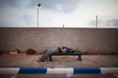 A Palestinian man rests after crossing from the West Bank town of Qalqilya to work in the Jewish state in the early morning of September 11 2011 near...