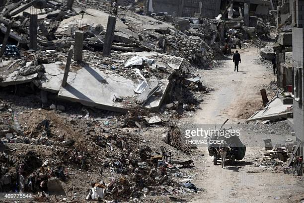 A Palestinian man rides a cart on April 15 2015 past the rubble of heavily damaged buildings in the eastern Gaza City neighborhood of Shejaiya which...