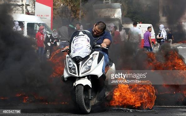 A Palestinian man rides his motorcycle past burning tires as protestors clash with Israeli security forces at the Hawara checkpoint south of the West...