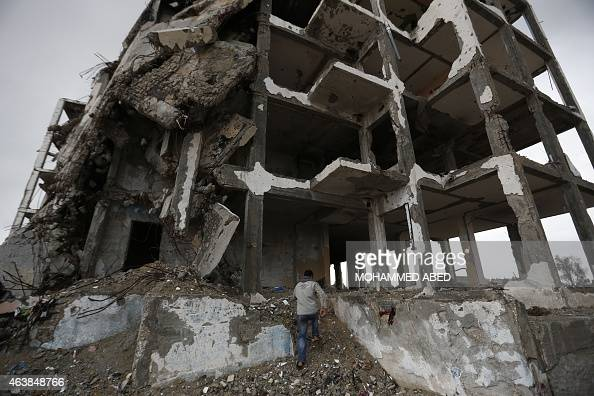 A Palestinian man runs into the ruins of a building that was destroyed by Israeli shelling during a 50day war in the summer of 2014 to take cover...