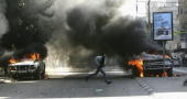 A palestinian man runs past burning vehicles belonging to the local electricity company on December 20 2006 in Gaza city Gaza Strip The vehicles were...