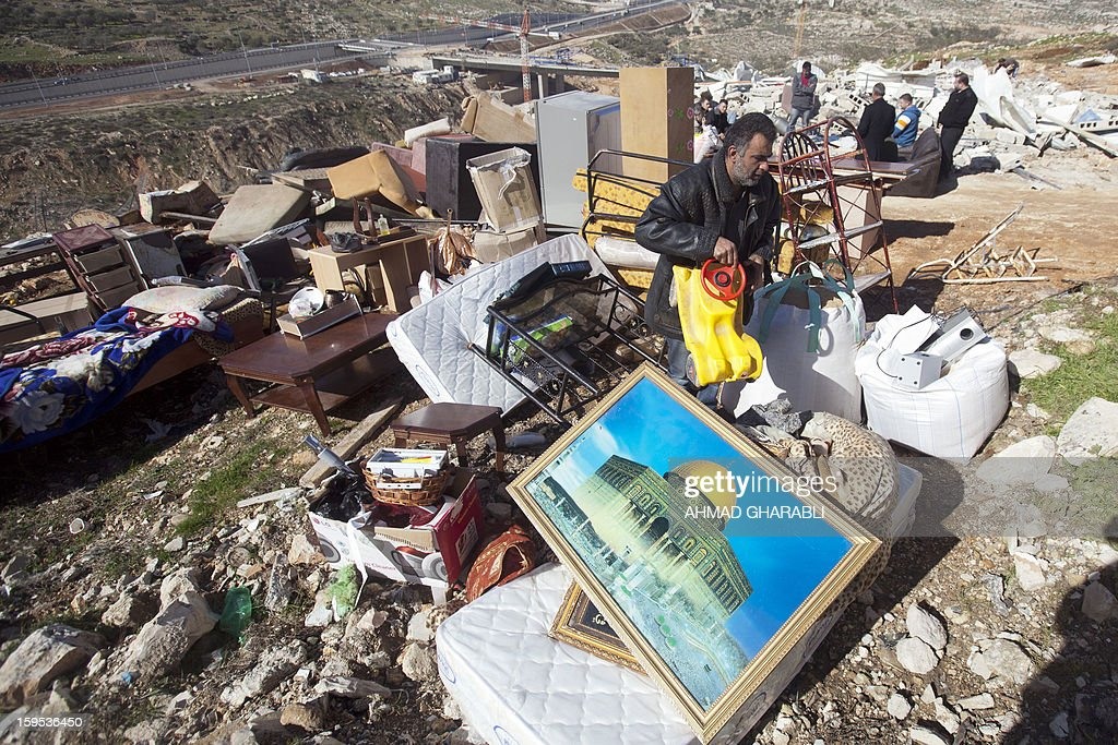 A Palestinian man salvages belongings from his home that was demolished by Israeli bulldozers in the Arab East Jerusalem neighbourhood of Beit Hanina, on January 15, 2013. Palestinian homes are usually demolished by Israeli authorities after being deemed illegally built. AFP PHOTO/AHMAD GHARABLI