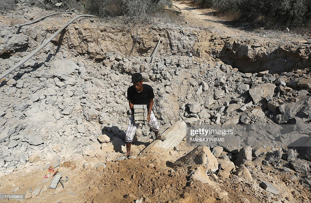 A Palestinian man salvages bricks following an Israeli air raid on al-Zawaida in the central Gaza strip early on June 24, 2013. The Israeli air force (IAF) attacked targets in the Gaza Strip following rocket fire from the Palestinian territory into southern Israel, sources from both sides of the conflict said. AFP PHOTO/MAHMUD HAMS