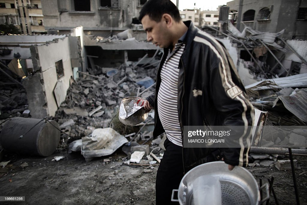 A Palestinian man salvages items from his damaged house following Israeli air strikes on the village of Beit Lahia in the northern Gaza Strip on November 18, 2012. Israeli war planes hit a Gaza City media centre and homes in northern Gaza in the early morning, as the death toll mounted, despite suggestions from Egypt's President Mohamed Morsi that there could be a 'ceasefire soon.' AFP PHOTO/MARCO LONGARI