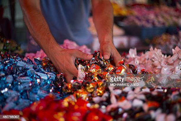A Palestinian man sells sweets at a Gaza City market on July 15 ahead of the Eid alFitr festivities celebrating the end of the holy Muslim fasting...