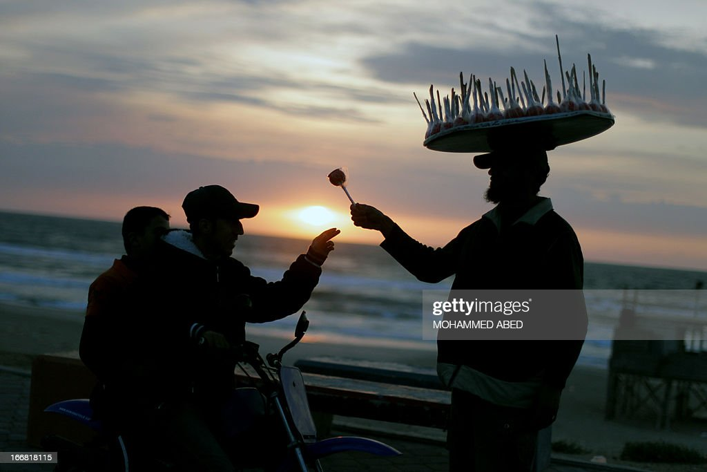A Palestinian man sells toffee apples at a beach in Gaza City during sunset on April 17, 2013, as Palestinians across the West Bank and Gaza Strip marked Prisoners' Day with a series of low-key rallies, as inmates themselves staged a hunger strike.