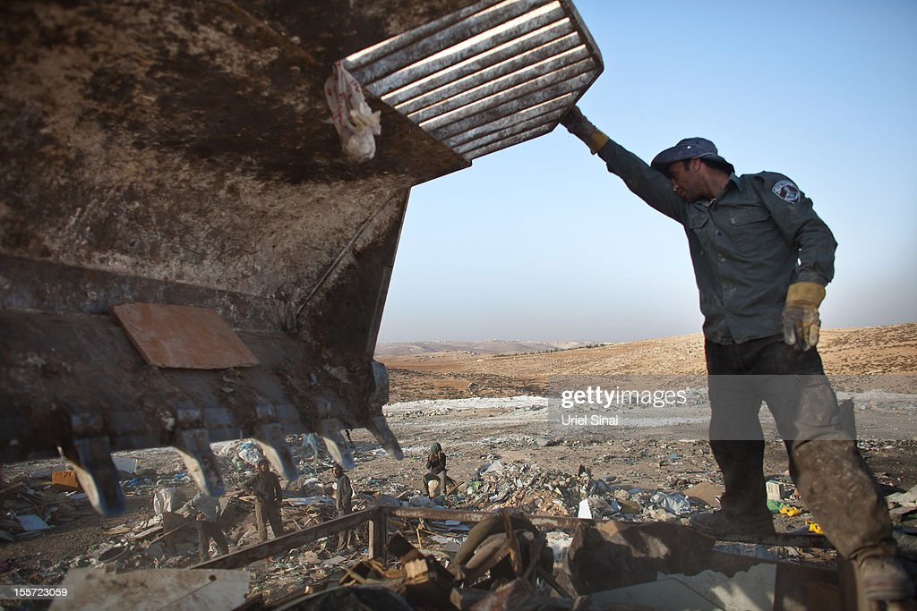 A Palestinian man sifts through a garbage dump on November 7, 2012 south of Hebron, West Bank. About 40 Palestinain men and children work at the West Bank garbage dump looking for clothing, metal and wood discarded, in large part, from the Jewish settelment in the region.