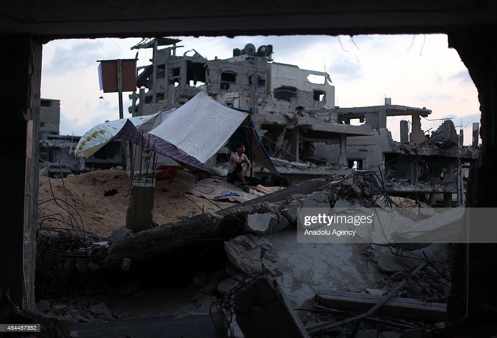 A Palestinian man sits among the debris of destroyed buildings as Palestinians start to return their homes during ceasefire in al-Shaaf neighborhood Gaza City, Gaza on August 31, 2014.